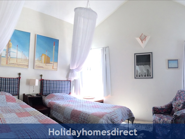 Villa Madrigal - By The Beach With Pool And Marina View: A spacious Twin Bedroom with room for a cot.