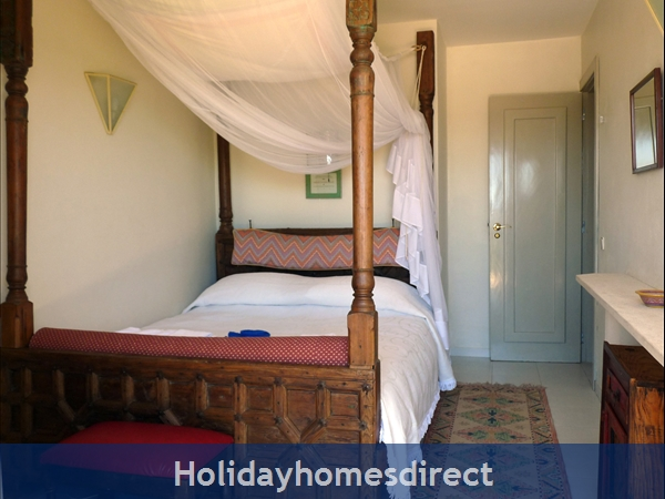 A cosy four-poster bed in the Garden Suite